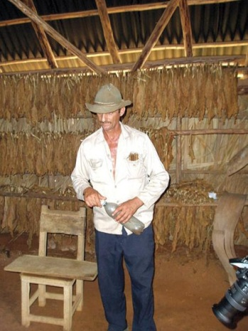 A farmer explains how the leaves of the tobacco plant are dried to produce the famous Cuban cigars. (Carolyn Tomlin)